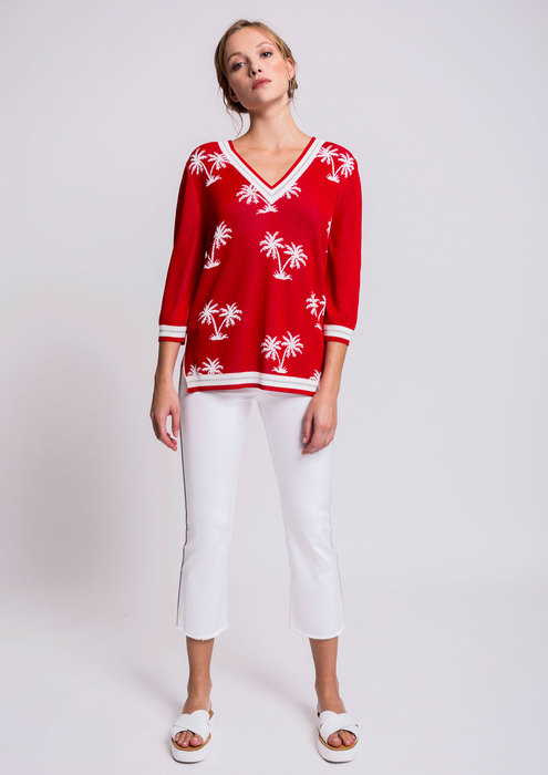 Red palm print sweater with white trousers