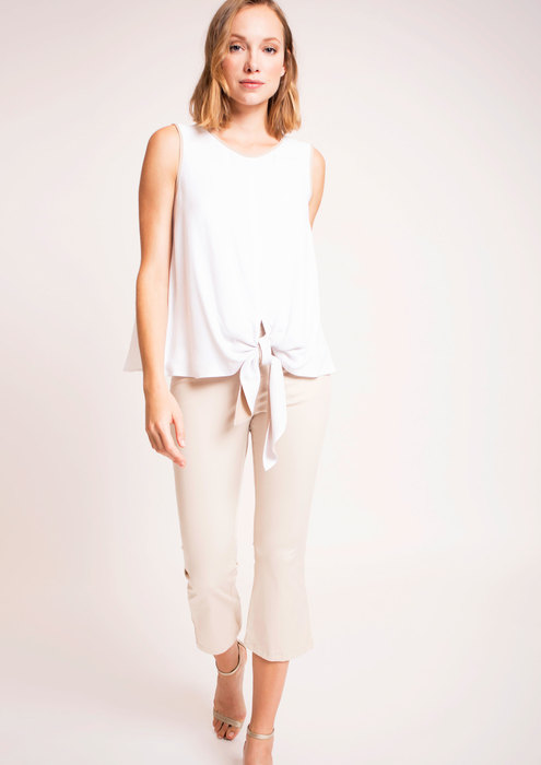 White top with bow and beige trousers
